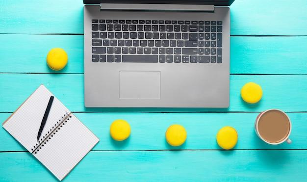 Espacio de trabajo con computadora portátil, cuaderno y bolígrafo. desayuno de la mañana con macarrones y una taza de café en una mesa de madera azul. almuerzo de negocios. el concepto de trabajo independiente, trabajo remoto. endecha plana. vista superior.