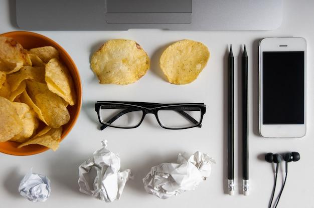 Espacio de trabajo con computadora portátil, papel arrugado y tazón de papas fritas en la mesa de madera. concepto de malos hábitos