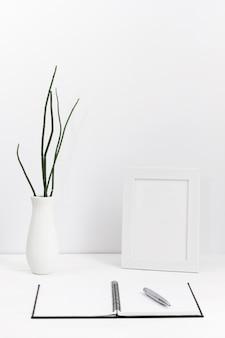 Espacio de trabajo contemporáneo con agenda en blanco y jarrón con marco.