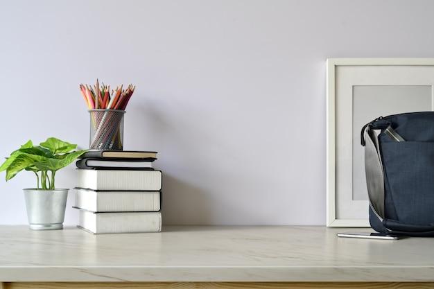 Espacio de trabajo y copia, escritorio blanco y maquetas, póster y mochila.