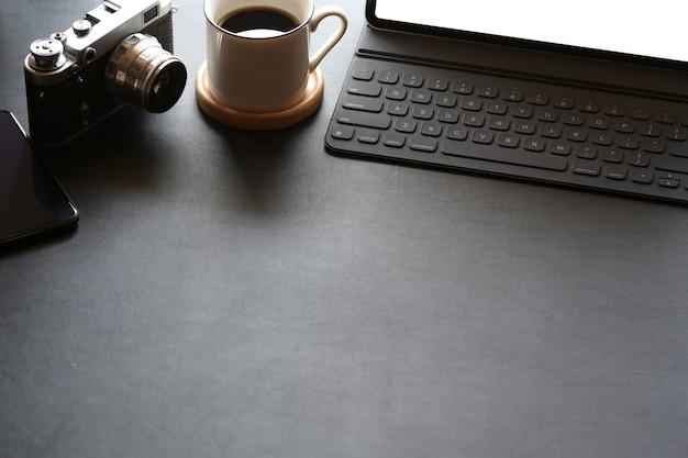 Espacio de trabajo creativo con cámara, tableta y espacio de copia.