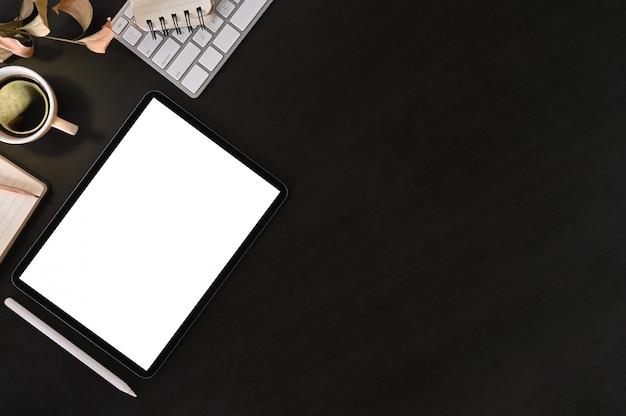 Espacio de trabajo creativo del escritorio con la tableta de la maqueta y el material de oficina en la tabla negra, visión superior.