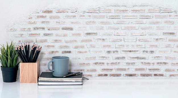 Espacio de trabajo creativo de maqueta con papelería, taza y planta de interior en la mesa superior blanca, espacio de copia.
