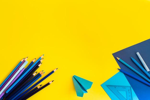 Espacio de trabajo creativo, moderno, minimalista, escolar o de oficina con suministros azules en amarillo