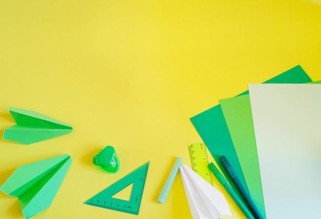 Espacio de trabajo creativo, moderno, minimalista, escolar o de oficina con suministros verdes en amarillo