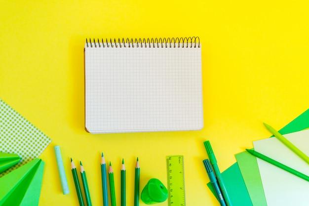 Espacio de trabajo creativo, moderno, minimalista, escolar o de oficina con suministros verdes y cuaderno de espiral en amarillo