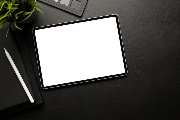 El espacio de trabajo creativo oscuro con tableta digital incluye accesorios de pantalla de trazado de recorte y espacio de copia