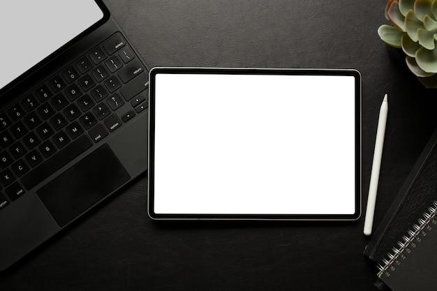 El espacio de trabajo creativo oscuro con tableta digital incluye teclado de pantalla de trazado de recorte y vista superior de papelería