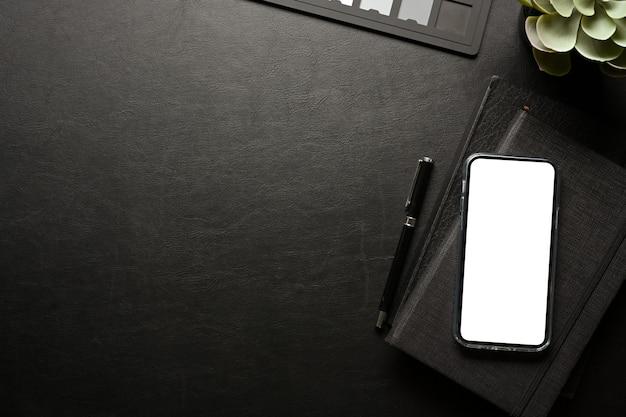 El espacio de trabajo creativo oscuro con teléfono inteligente incluye material de pantalla de trazado de recorte y vista superior del espacio de copia