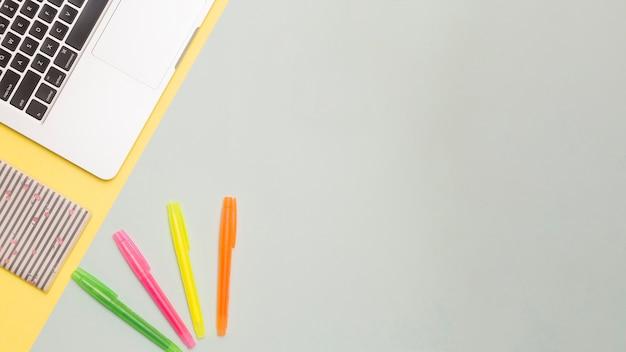 Espacio de trabajo creativo y plano con laptop y bolígrafos.
