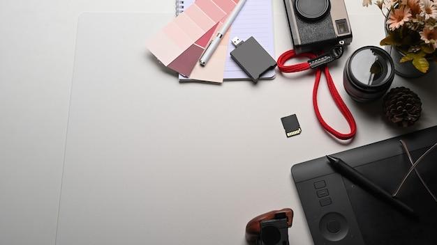 Espacio de trabajo creativo con tableta digital, cámara y planta en mesa blanca.