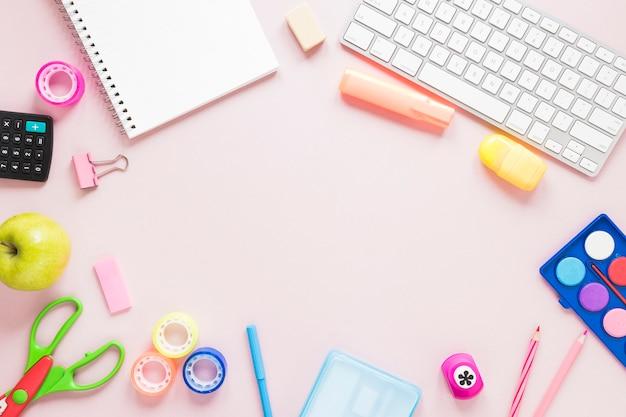 Espacio de trabajo creativo con teclado y útiles escolares.