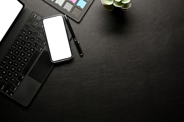 El espacio de trabajo creativo con teléfono inteligente incluye suministros de teclado de tableta de pantalla de ruta de recorte y vista superior del espacio de copia