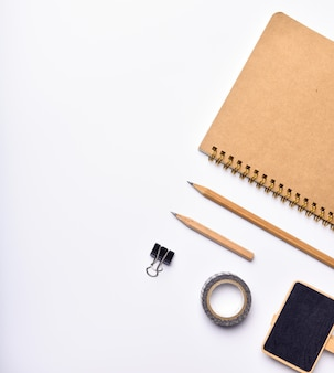Espacio de trabajo con cuaderno, lápiz y pizarra sobre fondo blanco.