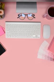 Espacio de trabajo de diseñador con computadora, muestra de color y gafas sobre fondo rosa.