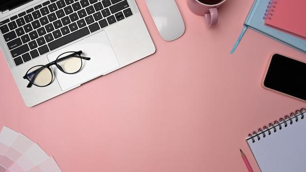 Espacio de trabajo de diseñador gráfico con computadora portátil, teléfono inteligente, gafas y cuaderno sobre fondo rosa.