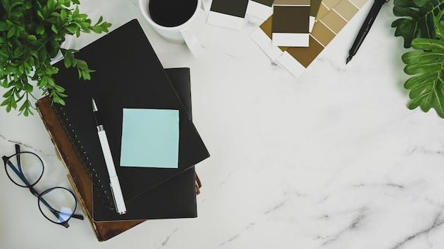 Espacio de trabajo de diseñador gráfico con cuaderno, vasos, taza de café, plantas de interior y muestras de color en la mesa de mármol.
