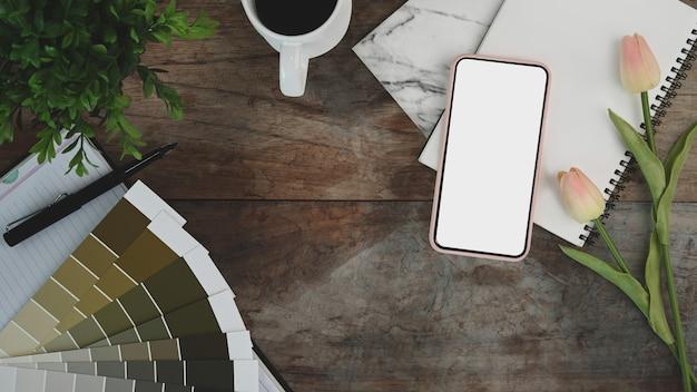 Espacio de trabajo de diseñador gráfico con portátil, teléfono inteligente, taza de café, plantas de interior y muestras de color en la mesa de madera.