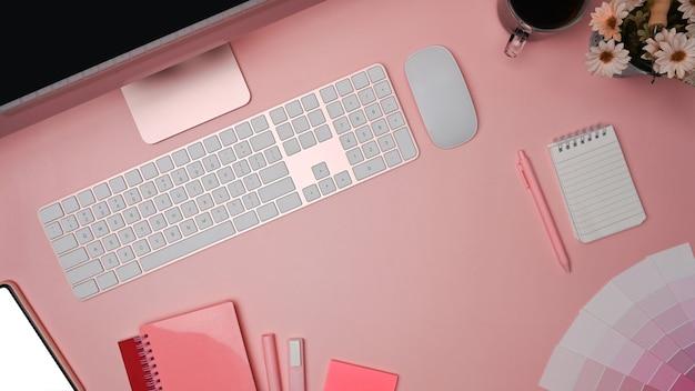 Espacio de trabajo de diseñador con muestras de computadora, teléfono móvil y colores sobre fondo rosa.