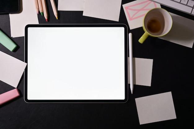Espacio de trabajo del diseñador con tableta de pantalla en blanco