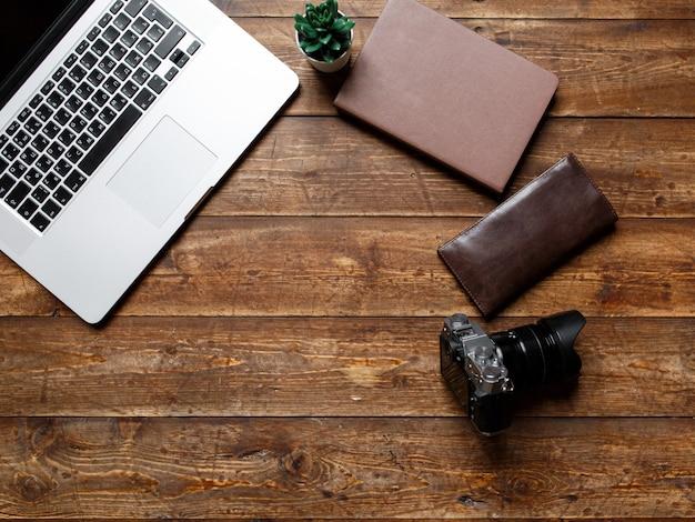 Espacio de trabajo de un empresario. vista desde arriba . cámara portátil y portátil en el escritorio con nota negra.