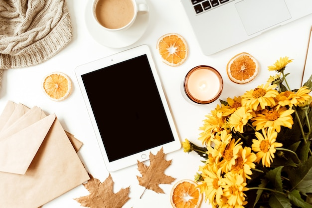 Espacio de trabajo de escritorio de mesa de oficina en casa plana con maqueta de tableta de espacio de copia en blanco, computadora portátil, taza de café, manta, sobres, hojas sobre una superficie blanca