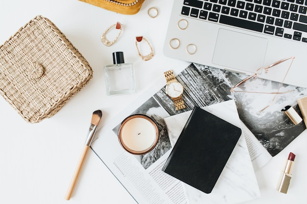 Espacio de trabajo de escritorio de oficina en casa moderno femenino con computadora portátil, perfume, reloj, lápiz labial, cepillo, accesorios en blanco