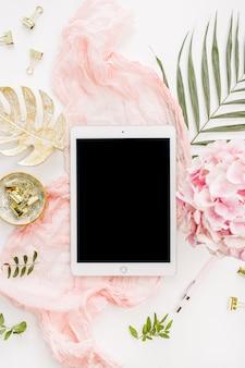 Espacio de trabajo de escritorio de oficina en casa moderno con tableta de pantalla en blanco, flores de hortensia rosa y accesorios