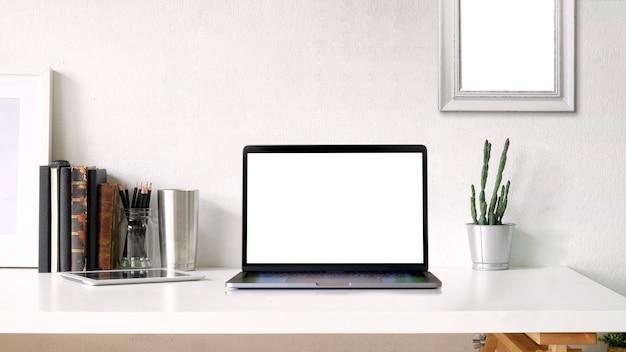 Espacio de trabajo y espacio de copia. cartel de maqueta y portátil de pantalla en blanco en el escritorio blanco