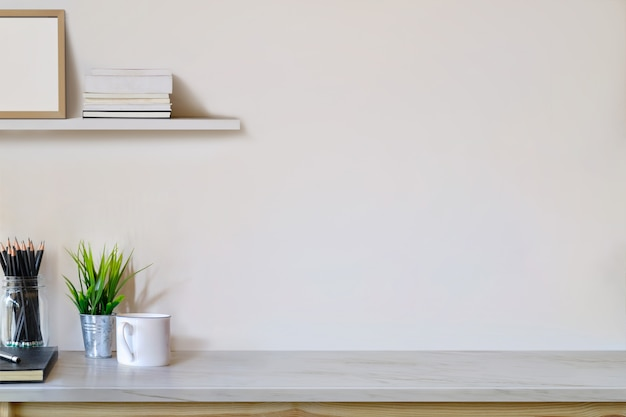 Espacio de trabajo y espacio para copiar, mesa de madera con planta, taza de café, póster de maquetas y esas cosas.
