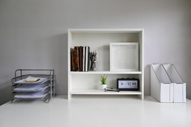 Espacio de trabajo con estantes y material de oficina en la mesa.