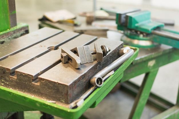 Espacio de trabajo en la fábrica. vicio, llave inglesa, máquina herramienta
