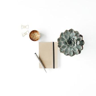 Espacio de trabajo femenino de la oficina en casa con suculentas, diarios y clips dorados