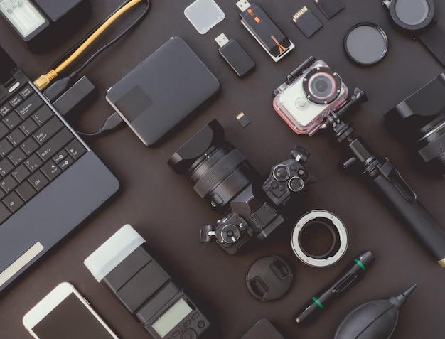 Espacio de trabajo de fotógrafo con cámara digital en el fondo de la mesa