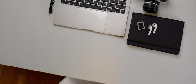 Espacio de trabajo de fotógrafo moderno con computadora portátil, cámara, agenda y espacio de copia