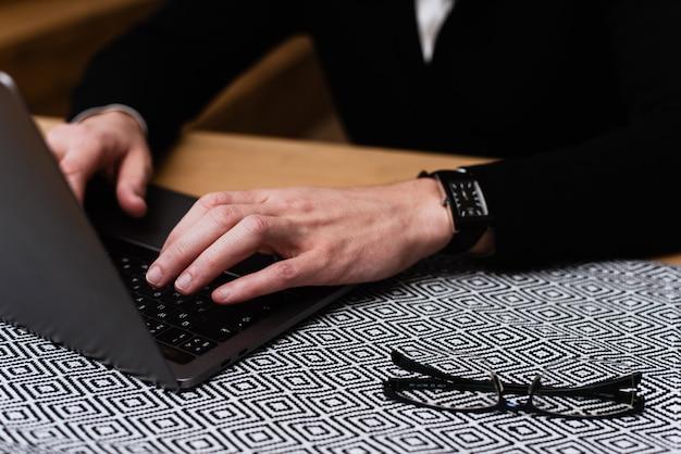 Espacio de trabajo de un joven oficinista. un hombre está escribiendo en una computadora portátil, buscando información, navegando en internet o trabajando desde su casa. concepto independiente
