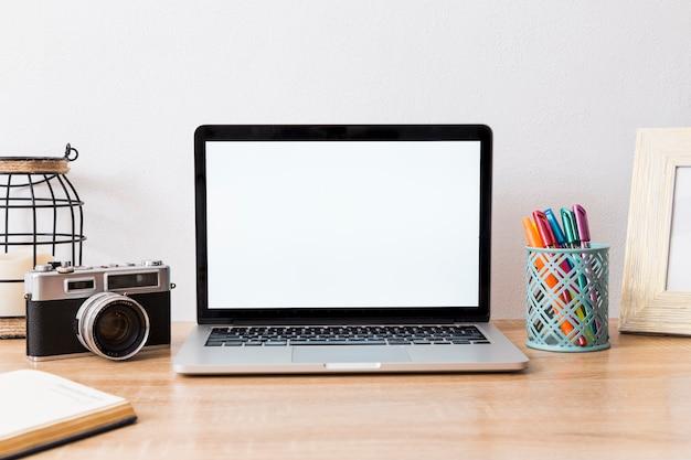 Espacio de trabajo con laptop y cámara en disposición.