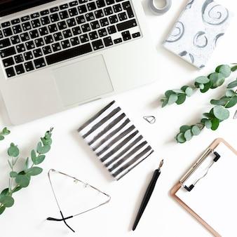 Espacio de trabajo con laptop, cuadernos, pluma de caligrafía, ramas de eucalipto, portapapeles, lentes