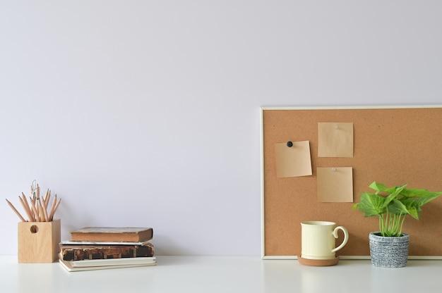 Espacio de trabajo con libros, café, plantas y papel de notas adhesivas a bordo de la oficina escritorio blanco.