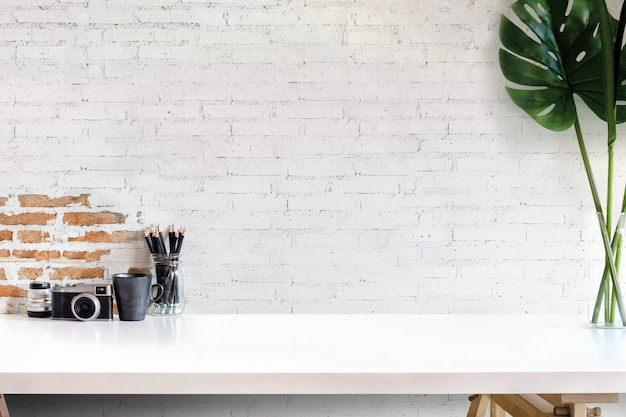 Espacio de trabajo de loft con equipo de fotógrafo en mesa de madera blanca en casa o estudio.