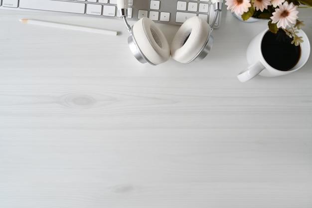 Espacio de trabajo de madera blanca con moderno teclado de escritorio y accesorios de oficina.