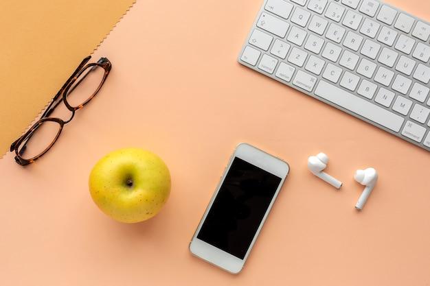 Espacio de trabajo con manzana, teclado, auriculares, teléfonos inteligentes y gafas.