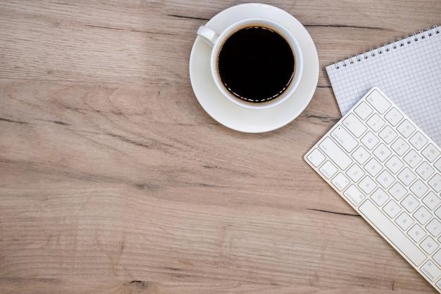 Espacio de trabajo con material de oficina y taza de café.