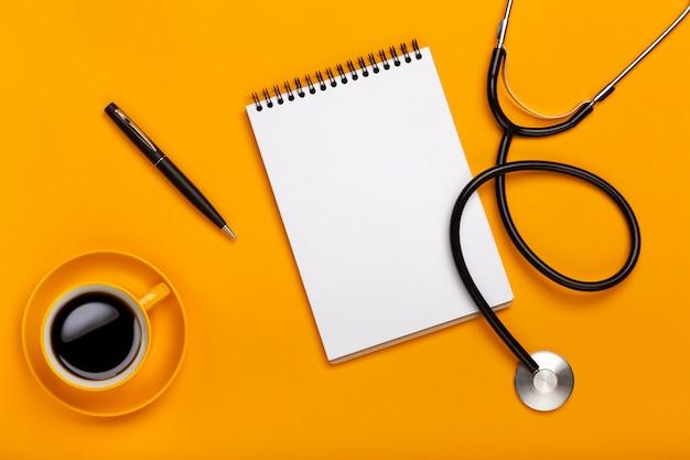 Espacio de trabajo médico con equipo médico en mesa amarilla con vista superior