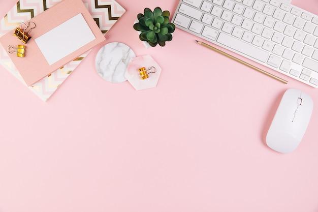 Espacio de trabajo de mesa de oficina rosa con un material de oficina