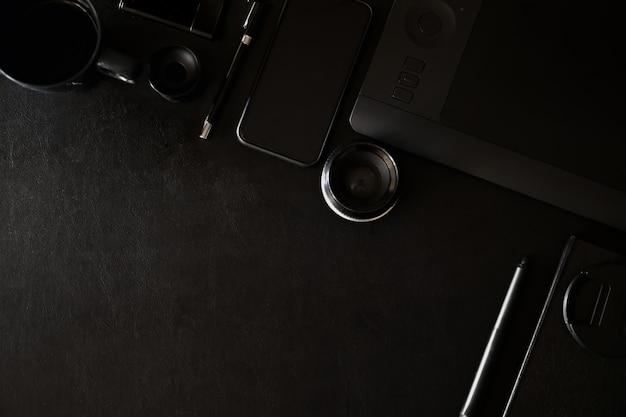 Espacio de trabajo en la mesa superior de cuero negro de un diseñador creativo o fotógrafo y espacio de copia