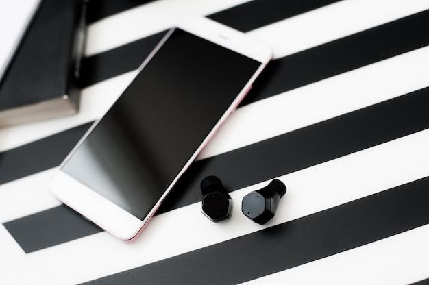Espacio de trabajo minimalista y elegante con teléfono inteligente simulado auriculares inalámbricos