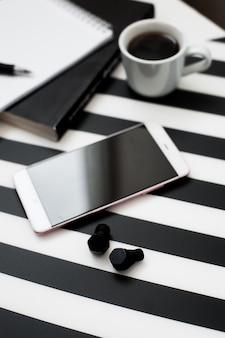 Espacio de trabajo minimalista y elegante con teléfono inteligente simulado, lápiz, taza de café, conexión inalámbrica