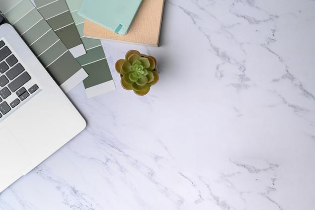 Espacio de trabajo mínimo con computadora portátil, muestra de color y cuaderno sobre fondo de mármol.