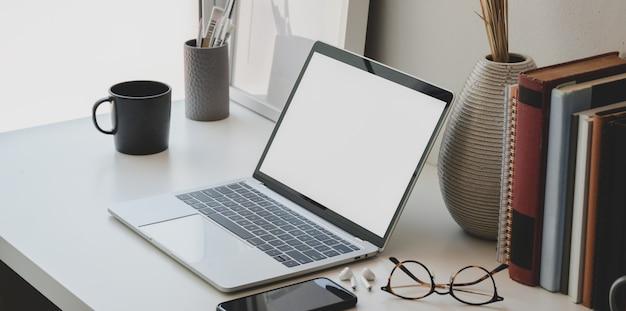 Espacio de trabajo mínimo con computadora portátil con pantalla en blanco, libros, florero de cerámica